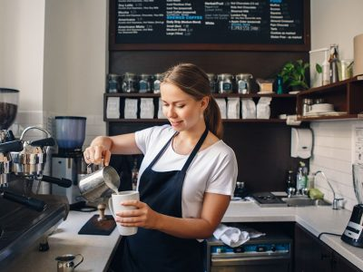 Portrait of smiling young Caucasian woman pouring hot milk in coffee. Waitress holding white mug cup in cafe. Person at work, small business concept